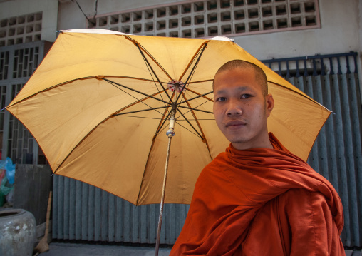 Cambodian monk walking in the street with umbrella, Phnom Penh province, Phnom Penh, Cambodia