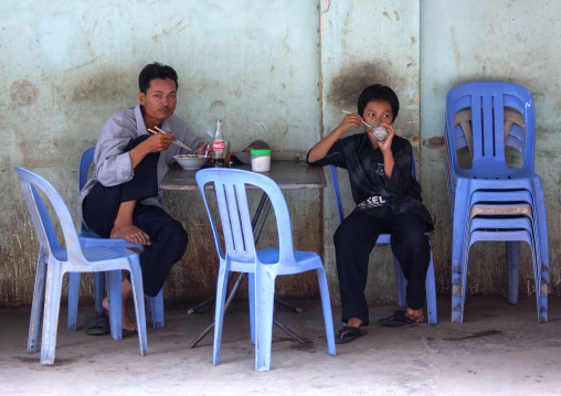 Father ans son eating in an outdoors restaurant, Phnom Penh province, Phnom Penh, Cambodia