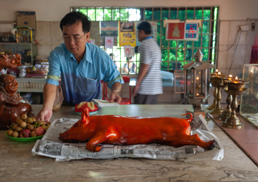 Cambodian man making offering with a roasted pig in a temple, Phnom Penh province, Phnom Penh, Cambodia