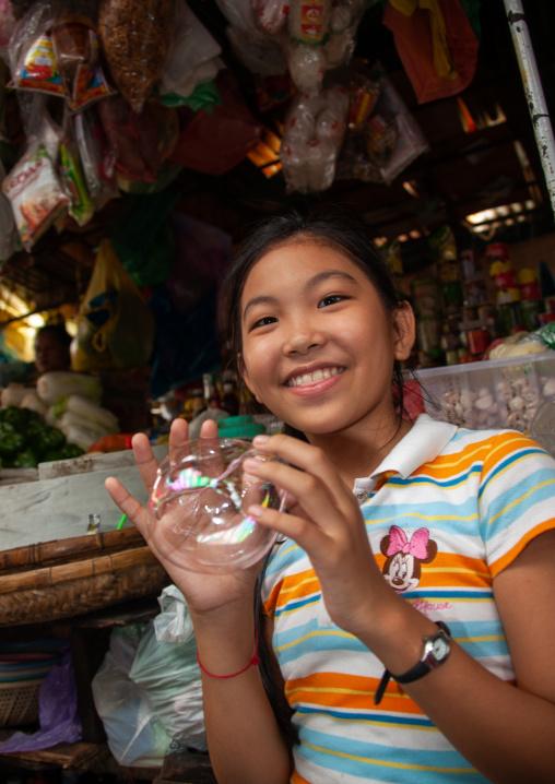 Portrait of a cambodian girl making bubbles in a market, Phnom Penh province, Phnom Penh, Cambodia