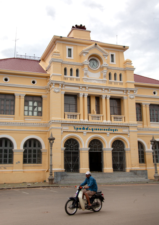 Cambodian man on a motorbike passing in front of the french-era post office, Phnom Penh province, Phnom Penh, Cambodia