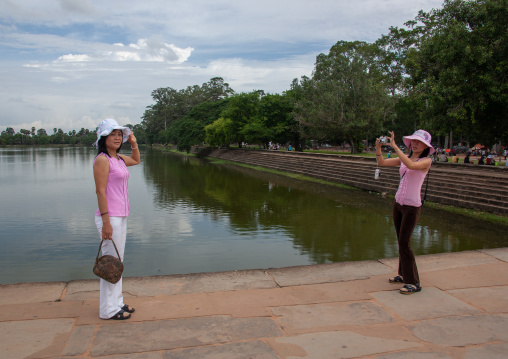 Tourists taking pictures in front of the Angkor wat pond, Siem Reap Province, Angkor, Cambodia