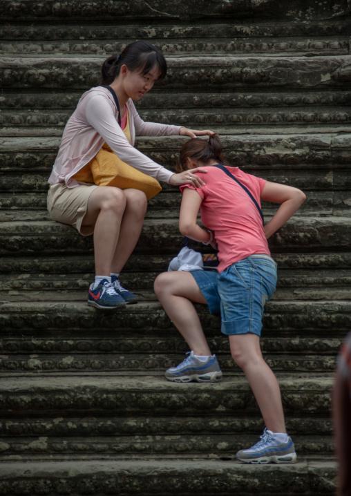 Asian tourists women climbing steps at Angkor wat, Siem Reap Province, Angkor, Cambodia