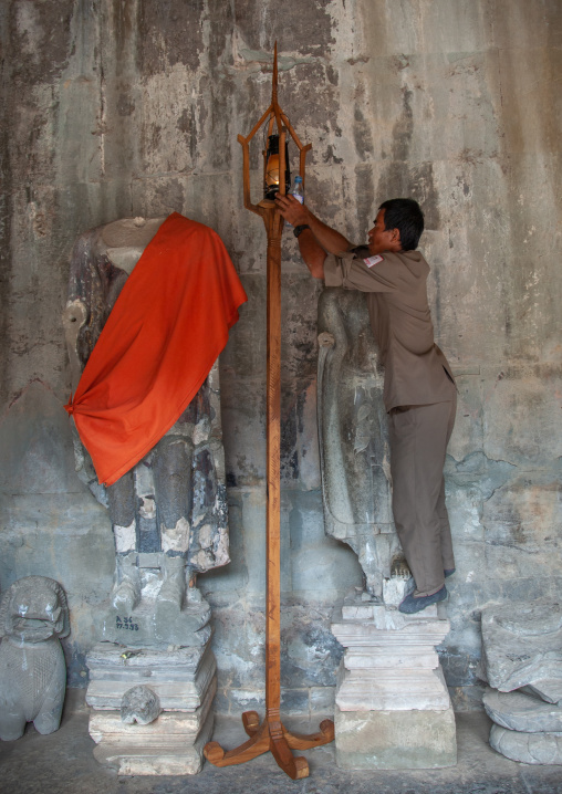 Cambodian guard putting a lamp in a temple, Siem Reap Province, Angkor, Cambodia