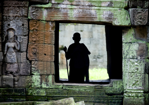 Monk silhouette standing in a temple vestige in Angkor wat, Siem Reap Province, Angkor, Cambodia