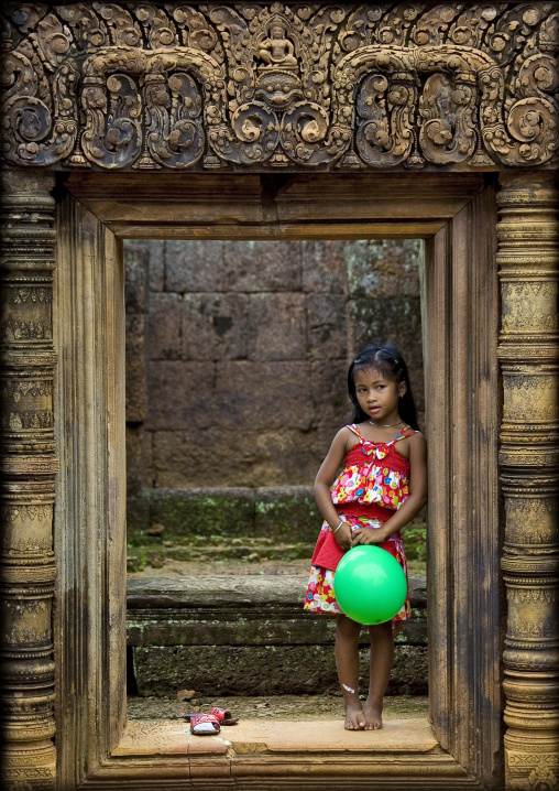 Cambodian little girl with a green balloon in Banteay Srei temple gate, Siem Reap Province, Angkor, Cambodia
