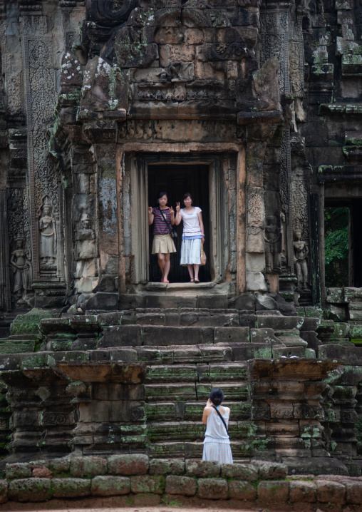 Asian tourists taking pictures in old ruins of a temple in Angkor wat, Siem Reap Province, Angkor, Cambodia