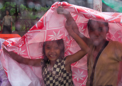 Cambodian children protecting themselves from the rain with a tablecloth, Siem Reap Province, Angkor, Cambodia