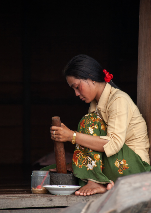 Cambodian woman using a mortar and pestle in the floating village on Tonle Sap lake, Siem Reap Province, Chong Kneas, Cambodia