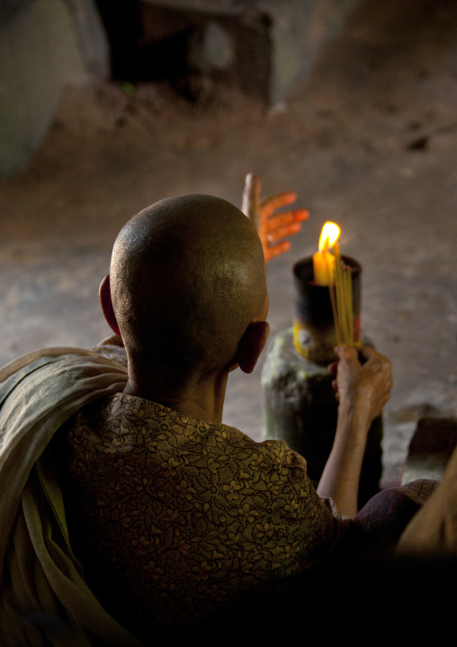 Female monk with a candle praying inside a tempe in Angkor wat, Siem Reap Province, Angkor, Cambodia