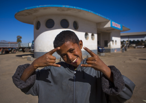 Boy Standing In Front Of A Service Station By Carlo Marchi And Carlo Montalbetti, Central region, Asmara, Eritrea