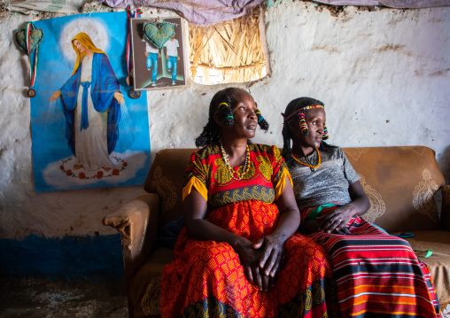 Portrait of Kunama tribe women with traditional hairstyles in front of a virgin mary poster, Gash-Barka, Barentu, Eritrea