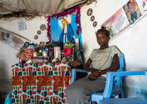 Eritrean Kunama tribe girl in front of a virgin mary poster in a home, Gash-Barka, Barentu, Eritrea