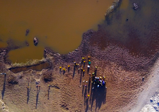 Aerial view of Borana tribe people filling jerricans in a water reservoir used for animals, Oromia, Yabelo, Ethiopia