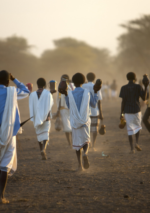 Rear View Of A Group Of Karrayyu Tribe Men In White Wrap Around Clothes Bringing Gifts For The Gadaaa Ceremony At Dawn, Metehara, Ethiopia