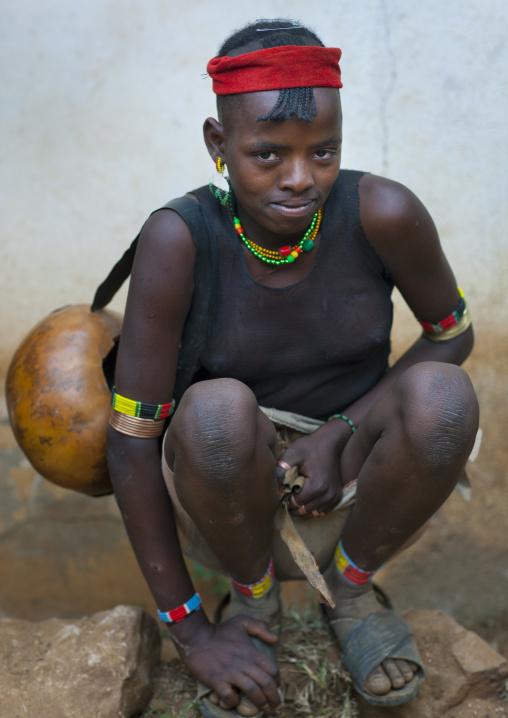 Shy squatting ari teenage girl omo valley Ethiopia