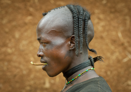 Portait of a fashionable tsemay tribe man with a traditional hairstyle posing in key afer, Omo valley, Ethiopia