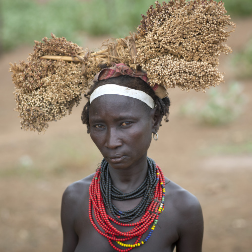 Dassanech Young Woman Wearing Beaded Necklaces And Holding Dried Plants On Her Head  Omo Valley Ethiopia