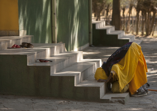 Old woman kissing the stairs of a church, Zway, Ehtiopia