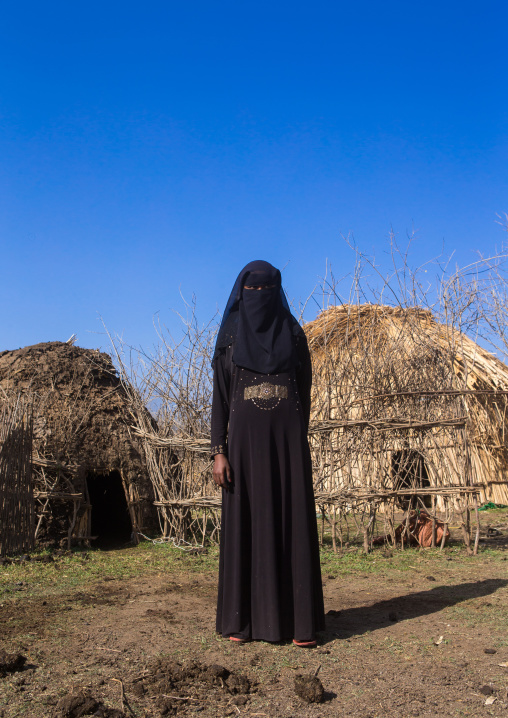 An ethiopian oromo woman dressed in black burqa stands in front of her hut, Amhara region, Artuma, Ethiopia