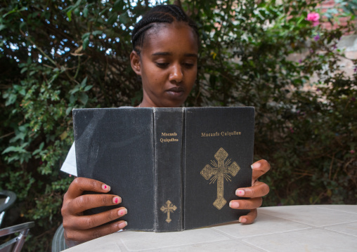 A karrayyu tribe girl called aliya reading bible in oromo language, Addis abeba region, Addis ababa, Ethiopia