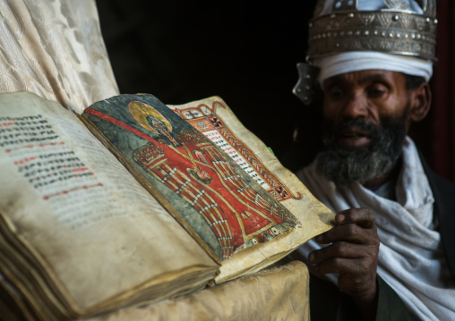 Ethiopian orthodox priest with an old bible in nakuto lab rock church, Amhara region, Lalibela, Ethiopia