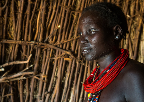 Toposa tribe woman with scarified face and red necklaces, Omo valley, Kangate, Ethiopia
