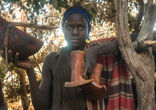 Circumcised boy from the dassanech tribe with their traditional wooden seat, Omo valley, Omorate, Ethiopia
