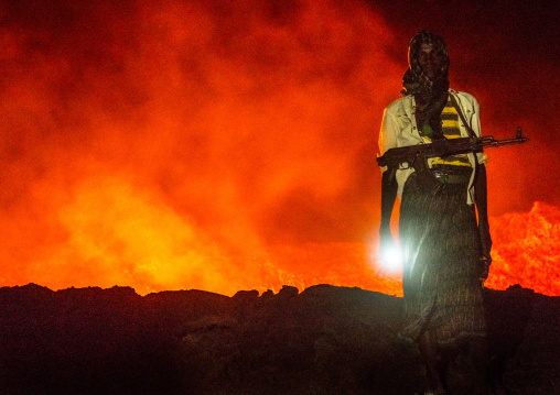 Afar guard in front of the living lava lake in the crater of erta ale volcano, Afar region, Erta ale, Ethiopia