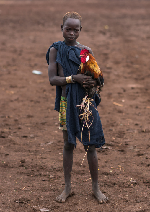 Bodi tribe boy with a rooster going to market, Omo valley, Hana mursi, Ethiopia