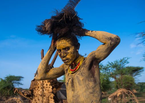 Dassanech man dressing with an ostrich feathers headwear for dimi ceremony to celebrate circumcision of the teenagers, Omo valley, Omorate, Ethiopia