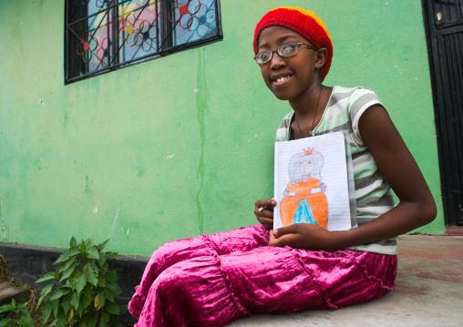 Rastafari girl called kizzy showing a princess she draws, Oromo, Shashamane, Ethiopia