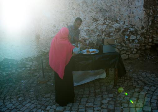 Woman buying samosas in the street, Harari region, Harar, Ethiopia