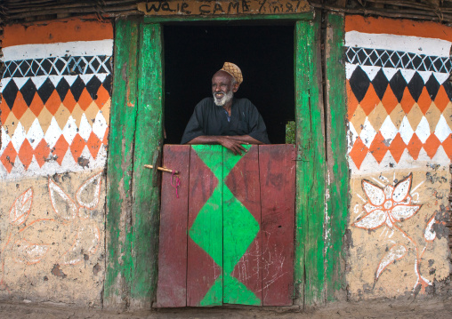 Ethiopia, Kembata, Alaba Kuito, ethiopian muslim man standing in front of his traditional painted house