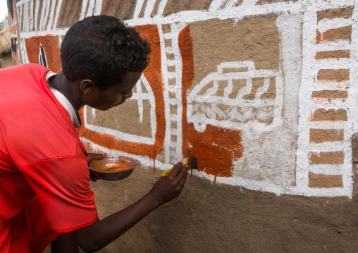 Ethiopia, Kembata, Alaba Kuito, young man painting the wall of a traditional ethiopian house
