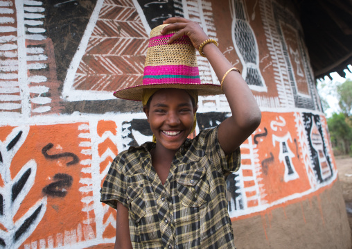Ethiopia, Kembata, Alaba Kuito, ethiopian woman with a hat standing in front of her traditional painted house