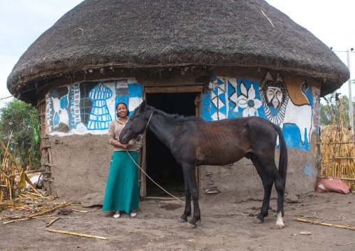Ethiopia, Kembata, Alaba Kuito, ethiopian woman standing in front of her traditional painted house with a horse