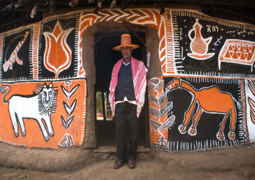 Ethiopia, Kembata, Alaba Kuito, ethiopian muslim man with a hat standing in front of his traditional painted house
