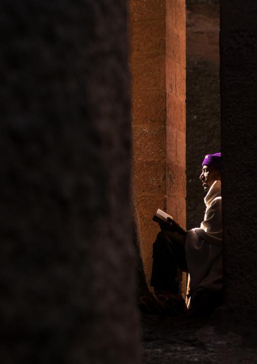 Lonely ethiopian orthodox man praying with a bible, Amhara region, Lalibela, Ethiopia