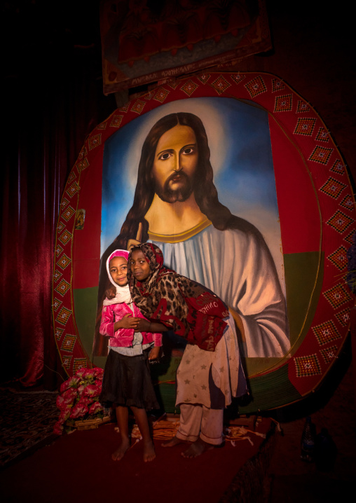 Children in medhane alem rock church in front of a huge painting of jesus, Amhara region, Lalibela, Ethiopia