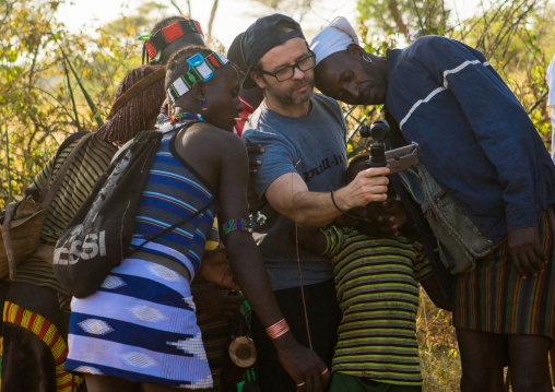 European tourist showing the screen of his camera to hamer tribe people, Omo valley, Turmi, Ethiopia
