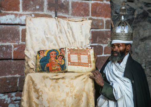 Ethiopian orthodox priest with an old bible in nakuto lab rock church, Amhara region, Lalibela, Ethiopia