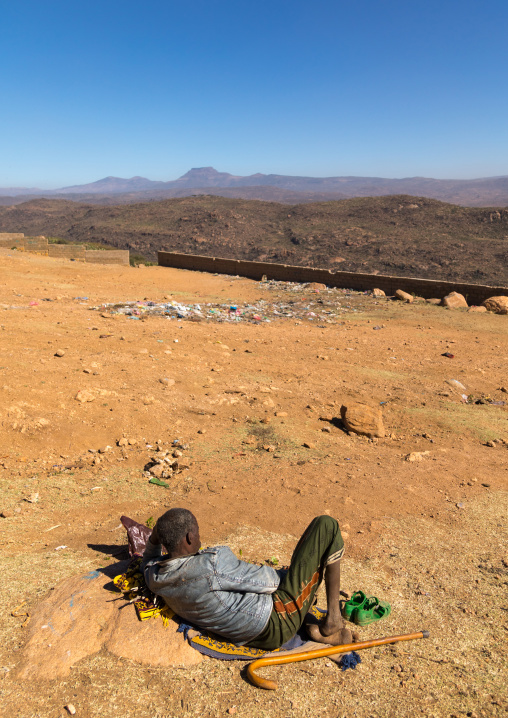 Ethiopian man chewing khat in front of a valley, Oromia, Babile, Ethiopia