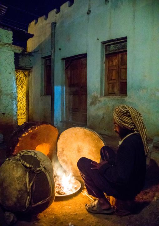 Harari man heating the drums before a ceremony in sufi community, Harari Region, Harar, Ethiopia