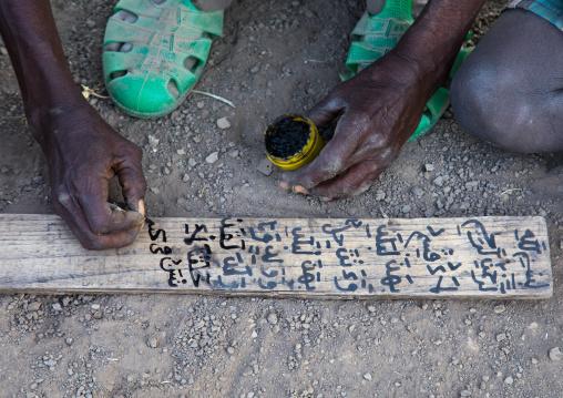 Afar tribe teacher writing on a wood board in a coranic school, Afar region, Afambo, Ethiopia