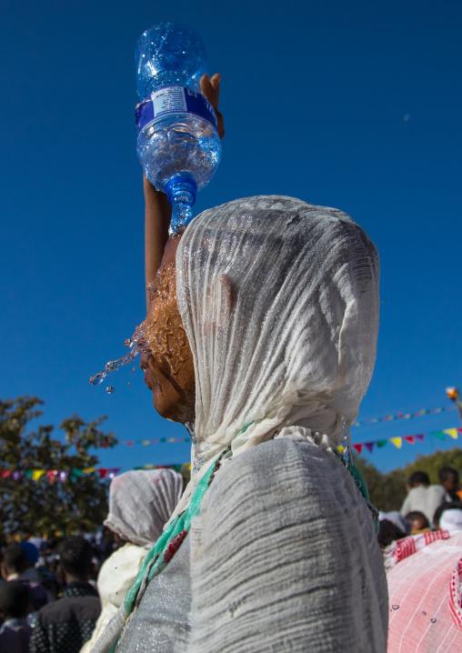Ethiopian pilgrim woman putting some holy water on her face during Timkat epiphany festival, Amhara region, Lalibela, Ethiopia
