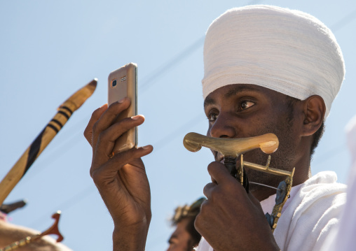 Priest of the ethiopian orthodox church taking pictures with his mobile phone, Amhara region, Lalibela, Ethiopia