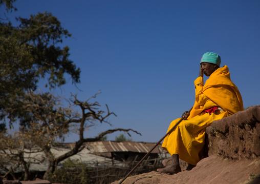 Lonely ethiopian monk woman in yellow shawl, Amhara region, Lalibela, Ethiopia