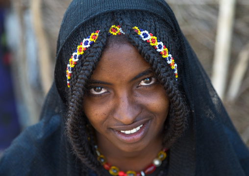 Portrait of a smiling Afar tribe girl with braided hair ands beaded headband, Afar region, Chifra, Ethiopia