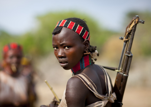 One Young Hamer Woman Holding Ak47 Looks Backwards At Bull Jumping Ceremony Omo Valley Ethiopia
